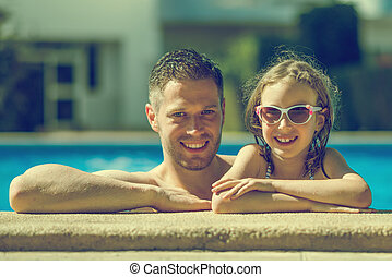 Smiling little girl with her dad in swimming pool.