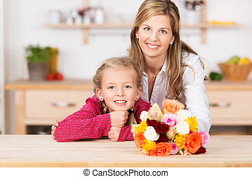 Smiling little girl with her mother and flowers