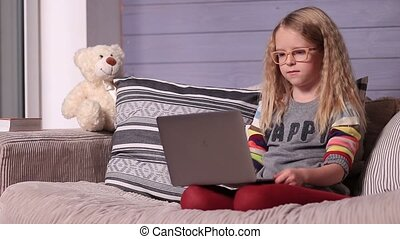 Smiling little girl with laptop computer at home