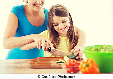 smiling little girl with mother chopping cucumber - family,...