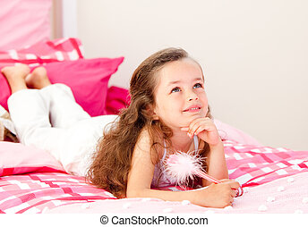 Smiling little girl writing on a notebook lying on her bed