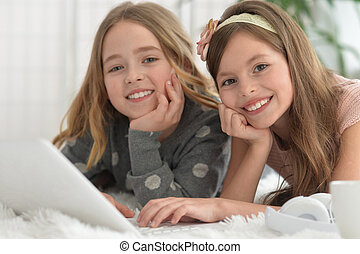 Smiling little girls using a laptop