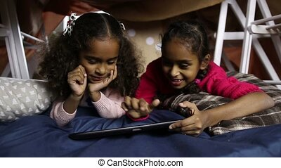 Smiling little girls working on digital tablet - Attractive...