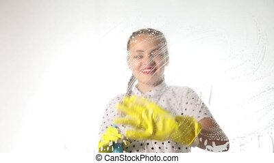 Smiling little housewife washed the window with a spray,...