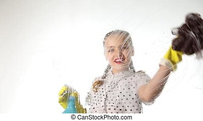 Smiling little housewife washed the window with a spray, cloth and detergent. Large glass in foam. Housework concept.