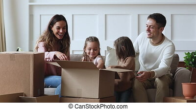 Playful family smiling little adorable kids sisters helping happy young couple parents unpacking belongings from huge cardboard boxes, sitting on sofa in new apartment home, moving day concept.
