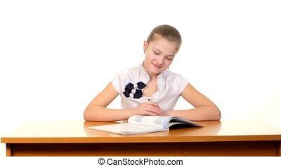 Smiling, little school girl reading the book, doing her homework on white background