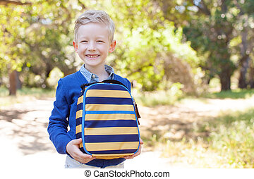 back to school concept - smiling little schoolboy holding...