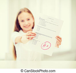 smiling little student girl with test and A grade -...