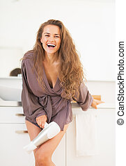 Smiling long hair woman with blow dryer in bathroom