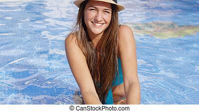 Smiling long haired beauty wearing bikini and hat