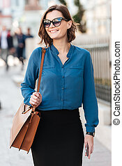 Smiling lovely woman in sunglasses on a street