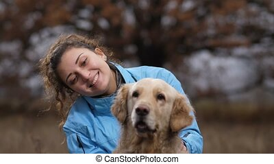 Smiling lovely woman with her dog in autumn nature