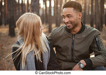 Smiling loving couple sitting outdoors in the forest.