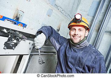 smiling machinist with spanner adjusting lift in elevator shaft