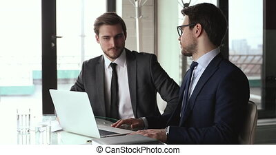 Smiling male business partners handshake use laptop find ...