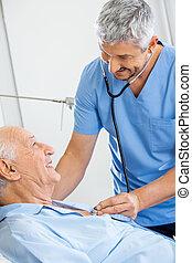 Smiling male caretaker examining senior man with stethoscope in bedroom at nursing home