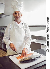 Smiling male chef cutting fish in kitchen