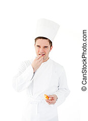 Smiling male chef eating fresh bread looking at the camera