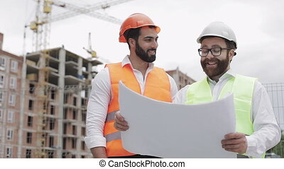 Smiling male construction engineer discussion with architect at construction site or building site of highrise building. They holding construction drawings in their hands.