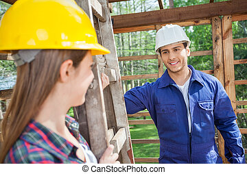Smiling Male Construction Worker Looking At Female Colleague