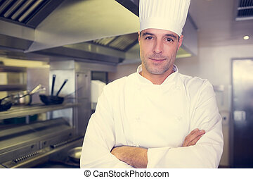 Smiling male cook with arms crossed in kitchen - Portrait of...