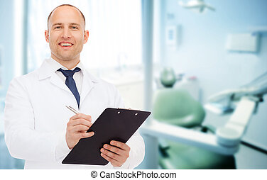 smiling male doctor with clipboard - medicine, profession,...