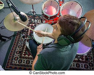 Smiling Male Drummer Wearing Headphones While Performing