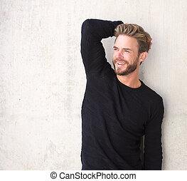 Smiling male fashion model posing in black sweater