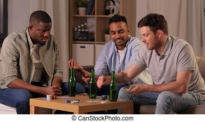 smiling male friends playing cards at home - leisure games, ...