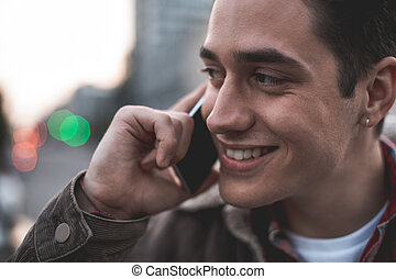 Smiling male making call on street