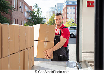 Smiling Male Mover Loading The Cardboard Boxes In Van
