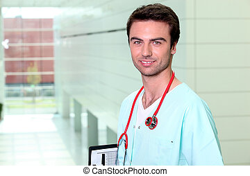Smiling male nurse alone in a corridor