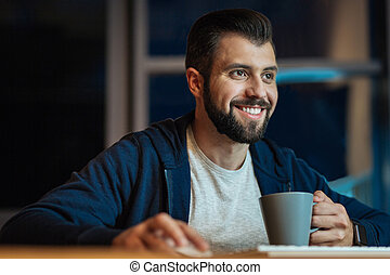 Smiling male person working at night