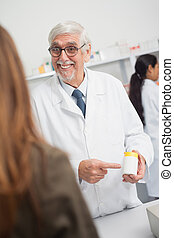 Smiling male pharmacist pointing at drugs