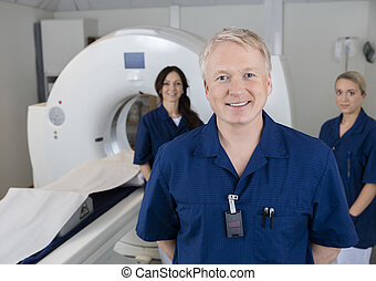 Smiling Male Radiologist With Colleagues Standing By MRI Machine