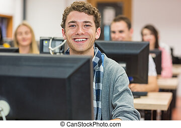 Smiling male student with others in computer room