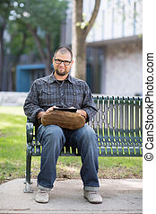Smiling Male University Student Sitting On Bench