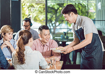 Smiling male waiter serving food in the restaurant