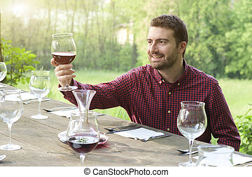 Smiling man admires red wine