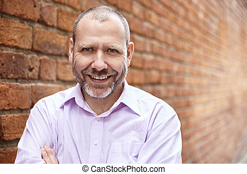 Smiling man against a brick wall