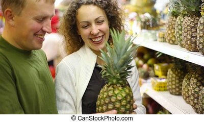 smiling man and woman buying pineapple in supermarket