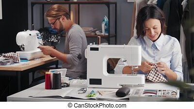 Smiling male and female designers working on sewing machines and talking at modern studio. Two happy people designing clothing in atelier.