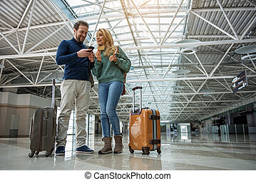 Smiling man and woman paying for boarding pass