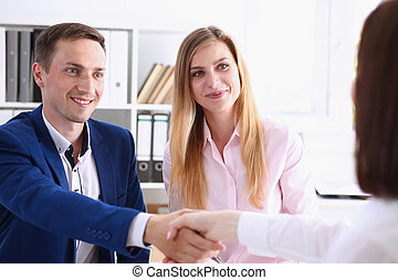 Smiling man and woman shake hands