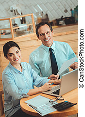 Smiling man and woman sitting at the table