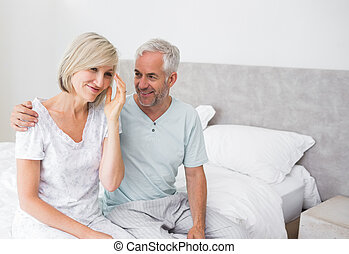 Smiling man and woman sitting on bed