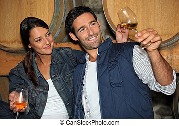 Smiling man and woman tasting wine in a cellar