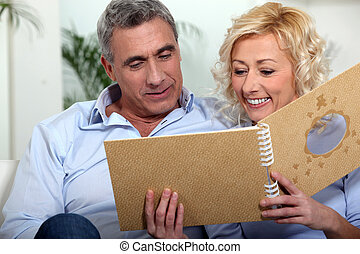Smiling man and woman watching a photo album