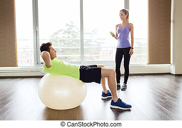 smiling man and woman with exercise ball in gym